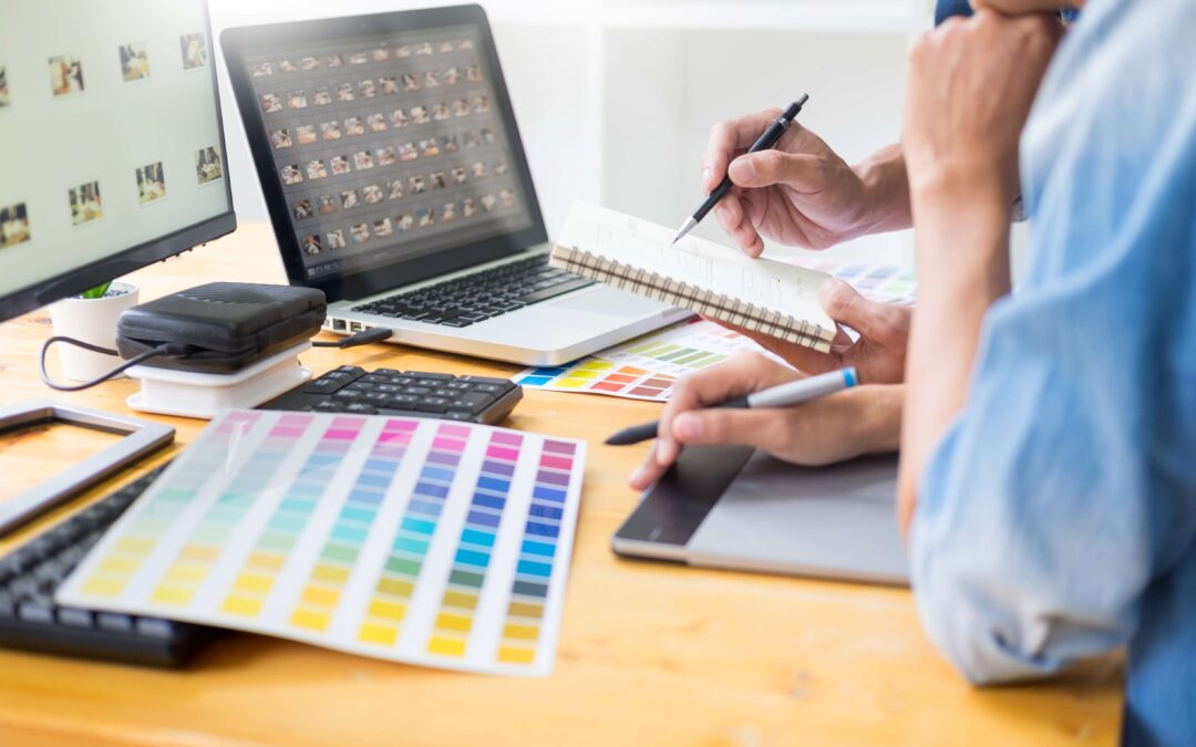 graphic designer team working on web design using color swatches editing artwork using tablet and a stylus At Desks In Busy Creative Office